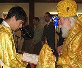 Acolyte, Nick Rolston, held the Prayer Book for His Eminence so he could read the prayers during the